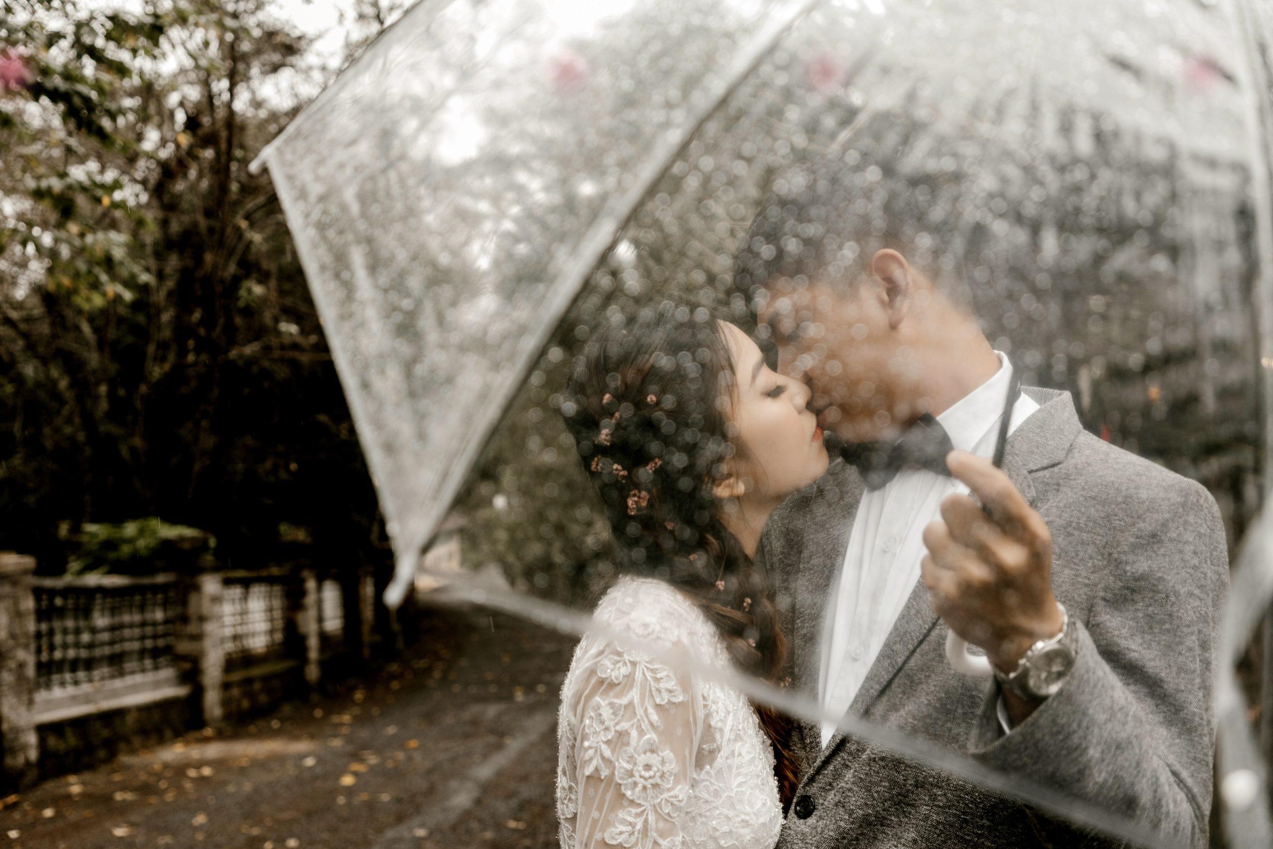 Para mloda stoi w deszczu na weselu
